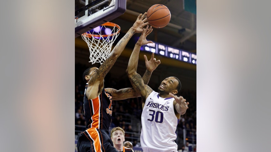 Washington's Desmond Simmons (30) and Oregon State's Eric Moreland reach for a rebound in the first half of an NCAA college basketball game Saturday, Feb. 16, 2013, in Seattle. (AP Photo/Elaine Thompson)