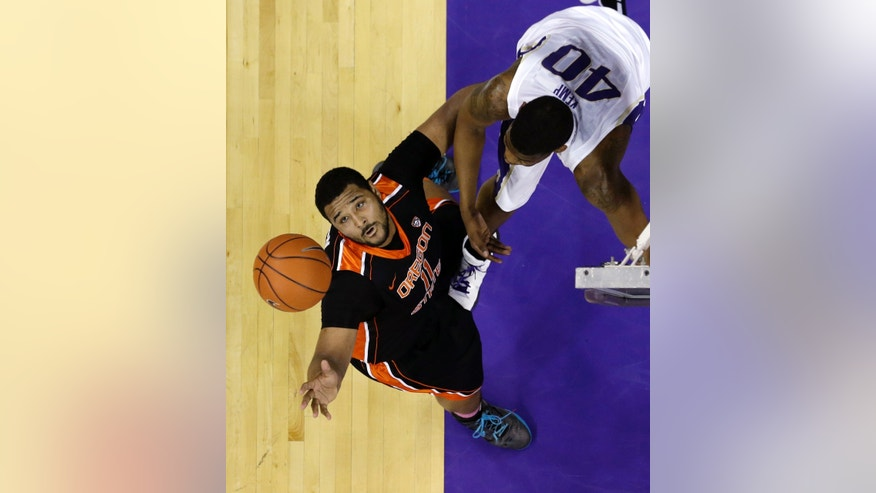 Oregon State's Joe Burton, left, reaches for a rebound in front of Washington's Shawn Kemp, Jr. in the first half of an NCAA college basketball game Saturday, Feb. 16, 2013, in Seattle. (AP Photo/Elaine Thompson)