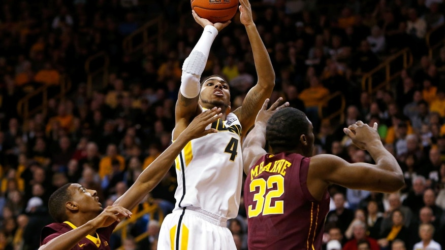Iowa guard Devyn Marble (4) shoots over Minnesota guard Austin Hollins (20) and forward Trevor Mbakwe (32) during the first half of an NCAA college basketball game, Sunday, Feb. 17, 2013, in Iowa City, Iowa. (AP Photo/Cedar Rapids Gazette, Brian Ray)