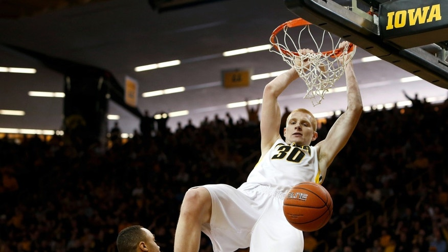 Iowa forward Aaron White (30) dunks over Minnesota guard Joe Coleman (11) during the first half of an NCAA college basketball game, Sunday, Feb. 17, 2013, in Iowa City, Iowa. (AP Photo/Cedar Rapids Gazette, Brian Ray)