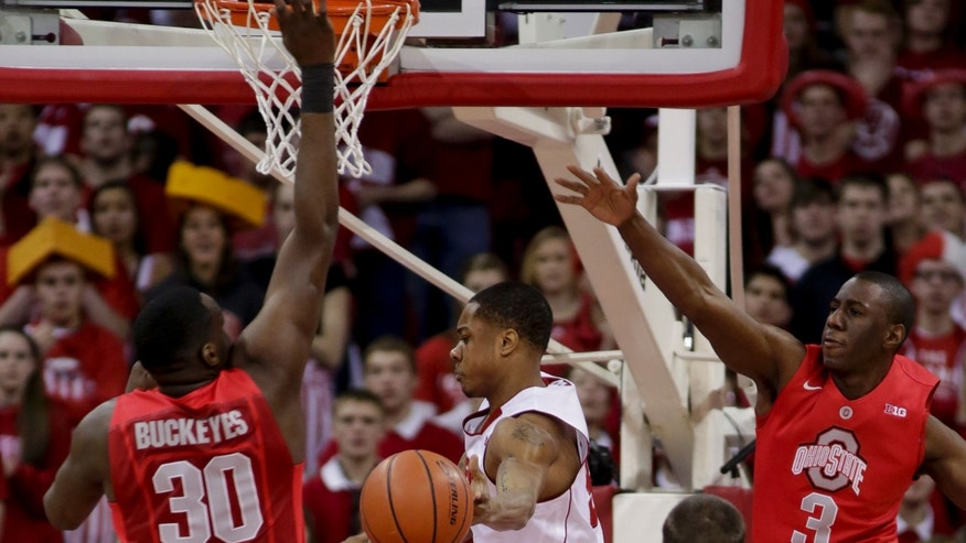 Wisconsin's George Marshall, center, passes against Ohio State's Evan Ravenel (10) and Shannon Scott (3) during the first half of an NCAA college basketball game on Sunday, Feb. 17, 2013, in Madison, Wis. (AP Photo/Andy Manis)