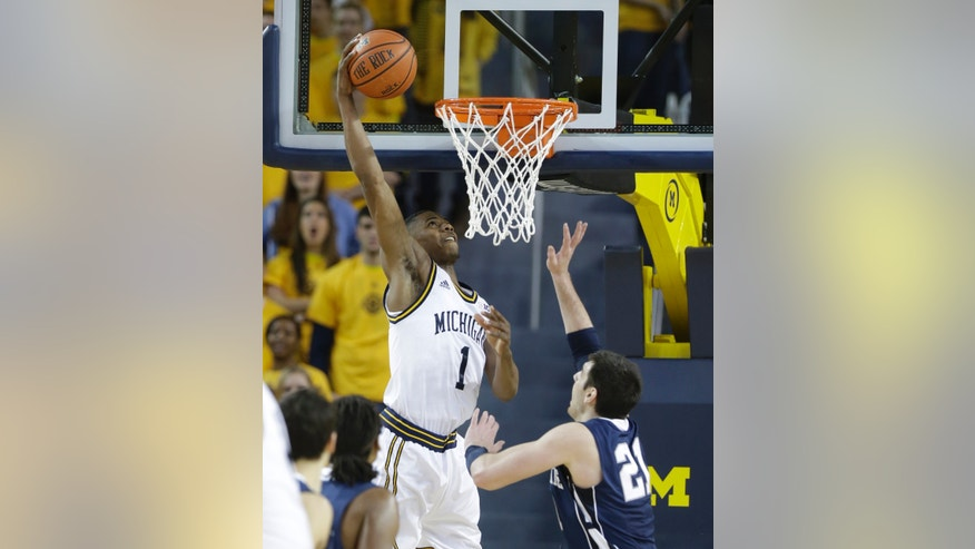 Michigan forward Glenn Robinson III (1) dunks over Penn State guard Nick Colella (20) during the first half of an NCAA college basketball game at Crisler Center in Ann Arbor, Mich., Sunday, Feb. 17, 2013. (AP Photo/Carlos Osorio)