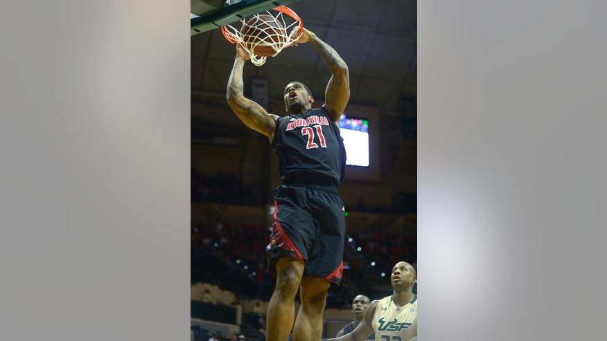 Louisville forward Chane Behanan (21) dunks in front of South Florida's Kore White, right, during the first half of an NCAA college basketball game in Tampa, Fla., Sunday, Feb. 17, 2013. (AP Photo/Phelan M. Ebenhack)