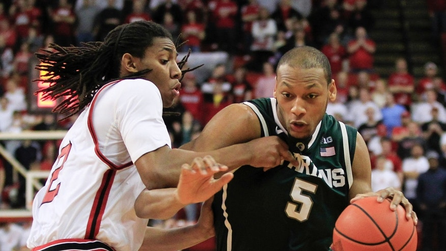 Michigan State's Adreian Payne (5) drives past Nebraska's David Rivers in the firs half of an NCAA college basketball game in Lincoln, Neb., Saturday, Feb. 16, 2013. (AP Photo/Nati Harnik)
