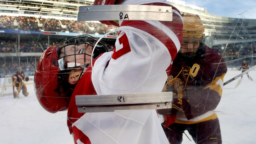 Wisconsin forward Derek Lee, left, is checked into the boards by Minnesota defenseman Ben Marshall during the first period of a college hockey game at Chicago's Soldier Field, Sunday, Feb. 17, 2013. (AP Photo/Charles Rex Arbogast)