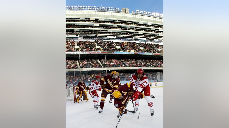 Minnesota forward Zach Budish (24) is checked to the ice by Wisconsin forward Michael Mersch (25) during the first period of a college hockey game at Chicago's Soldier Field, Sunday, Feb. 17, 2013. (AP Photo/Charles Rex Arbogast)