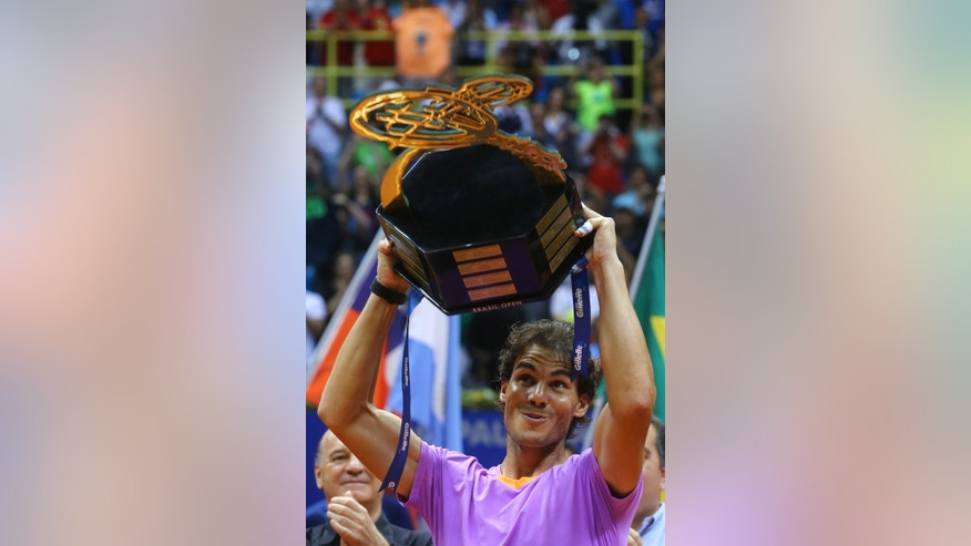 Spain's Rafael Nadal holds up the Brazil Open ATP tennis tournament trophy after defeating Argentina's David Nalbandian in the final match in Sao Paulo, Brazil, Sunday, Feb. 17, 2013. Nadal won 6-2, 6-3. (AP Photo/Andre Penner)