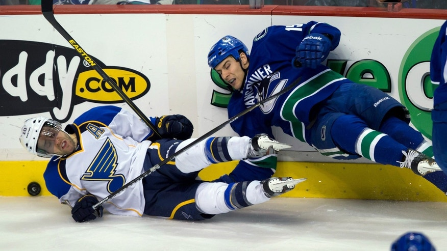 Vancouver Canucks' Aaron Volpatti, right, checks St. Louis Blues' Andy McDonald during the second period of an NHL hockey game in Vancouver, British Columbia, on Sunday, Feb. 17, 2013. (AP Photo/The Canadian Press, Darryl Dyck)