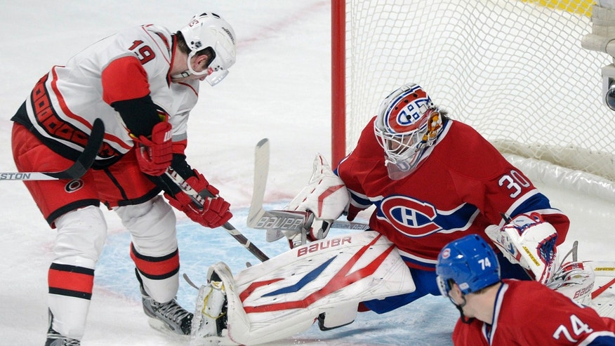 Montreal Canadiens goaltender Peter Budaj (30) makes a save against Carolina Hurricanes' Jiri Tlusty (19) as Canadiens' Alexei Emelin (74) defends during the first period of their NHL hockey game, Monday, Feb. 18, 2013, in Montreal. (AP Photo/The Canadian Press, Graham Hughes)