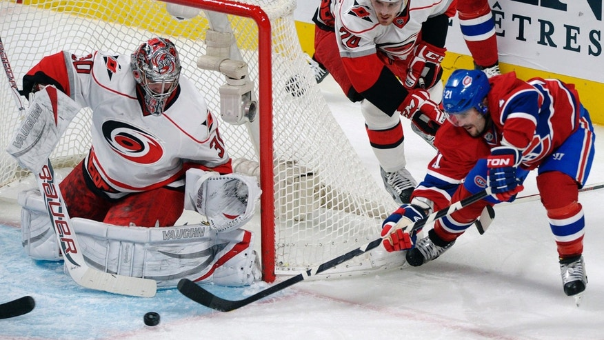 Carolina Hurricanes goaltender Can Ward (30) makes a save against Montreal Canadiens' Brian Gionta (21) as Hurricanes' Bobby Sanguinetti (24) defends during the second period of their NHL hockey game, Monday, Feb. 18, 2013, in Montreal. (AP Photo/The Canadian Press, Graham Hughes)
