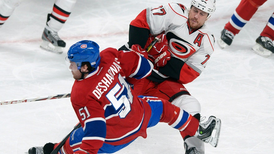 Montreal Canadiens' David Desharnais (51) collides with Carolina Hurricanes' Joe Corvo, right, during the second period of their NHL hockey game, Monday, Feb. 18, 2013, in Montreal. (AP Photo/The Canadian Press, Graham Hughes)