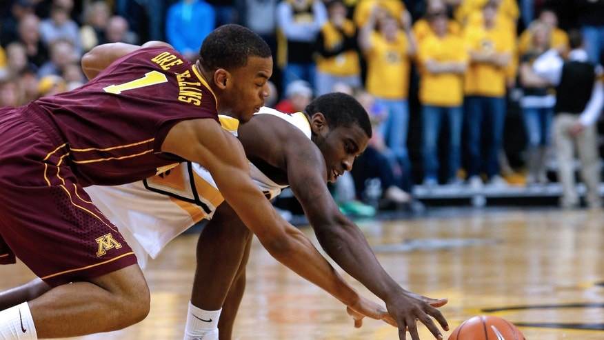 Iowa guard Anthony Clemmons (5) battles for a ball on the floor with Minnesota guard Andre Hollins (1) during the second half of an NCAA college basketball game, Sunday, Feb. 17, 2013, in Iowa City, Iowa. (AP Photo/Cedar Rapids Gazette, Brian Ray)