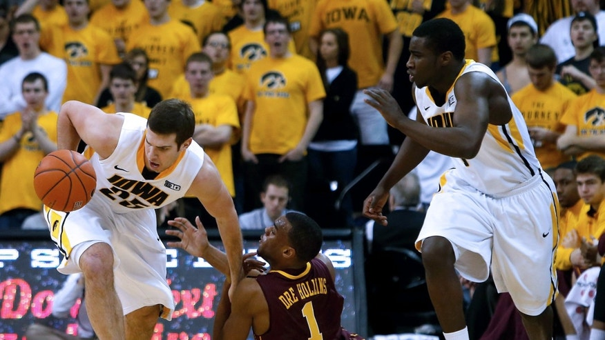 Iowa guard/forward Eric May (25) draws a foul as he steals the ball from Minnesota guard Andre Hollins (1) during the second half of an NCAA college basketball game, Sunday, Feb. 17, 2013, in Iowa City, Iowa. (AP Photo/Cedar Rapids Gazette, Brian Ray)