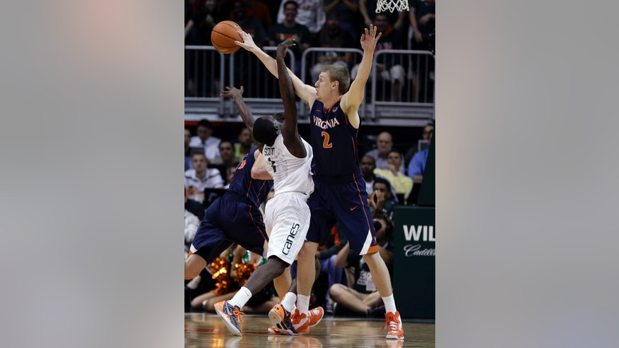 Virginia's Paul Jesperson (2) blocks a shot by Miami's Durand Scott (1) during the first half of an NCAA college basketball game in Coral Gables, Fla., Tuesday, Feb. 19, 2013. (AP Photo/J Pat Carter)
