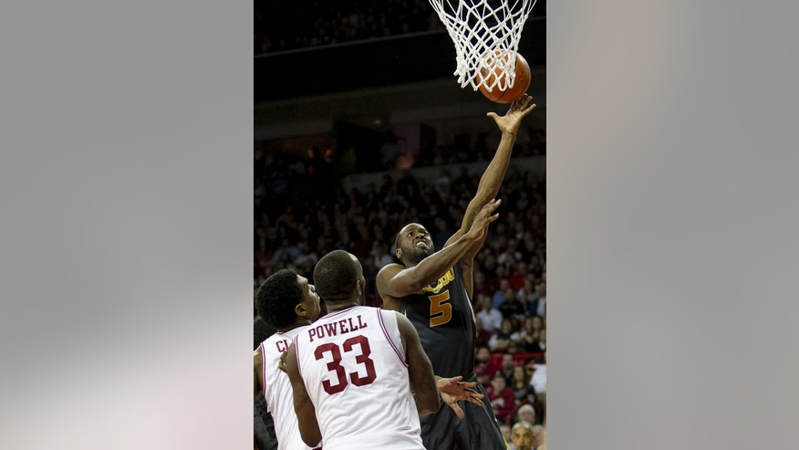 Missouri's Keion Bell (5) shoots a layup against Arkansas' Marshawn Powell (33) and Coty Clarke (4) during the second half an NCAA college basketball game in Fayetteville, Ark., Saturday Feb. 16, 2013. Arkansas defeated Missouri 73-71. (AP Photo/Gareth Patterson)