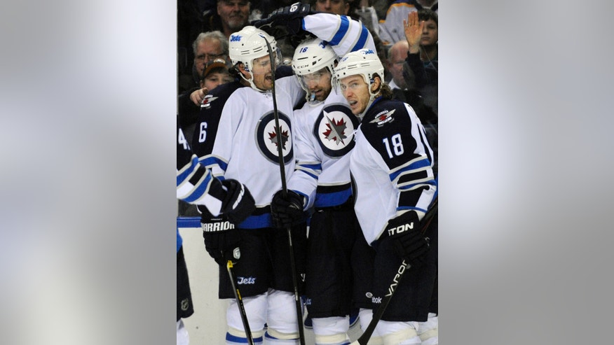 Winnipeg Jets' defenseman Ron Hainsey (6), left winger Andrew Ladd (16) and center Brian Little (18) celebrate a goal by Ladd during the second period of an NHL hockey game against the Buffalo Sabres in Buffalo, N.Y., Tuesday, Feb. 19, 2013. (AP Photo/Gary Wiepert)