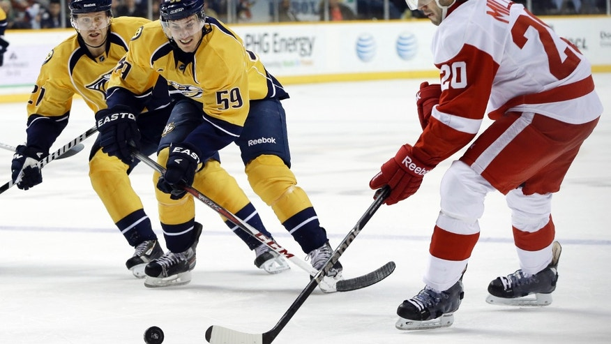 Detroit Red Wings left wing Drew Miller (20) passes the puck as Nashville Predators defenseman Roman Josi (59), of Switzerland, and right wing Patric Hornqvist (27), of Sweden, close in during the second period of an NHL hockey game Tuesday, Feb. 19, 2013, in Nashville, Tenn. (AP Photo/Mark Humphrey)