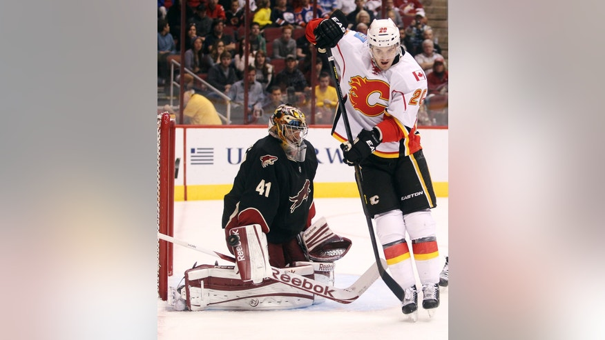 Phoenix Coyotes goalie Mike Smith (41) makes a blocker save as Calgary Flames left winger Curtis Glencross, right, sets a screen in the first period of an NHL hockey game, Monday, Feb. 18, 2013, in Glendale, Ariz. (AP Photo/Paul Connors)