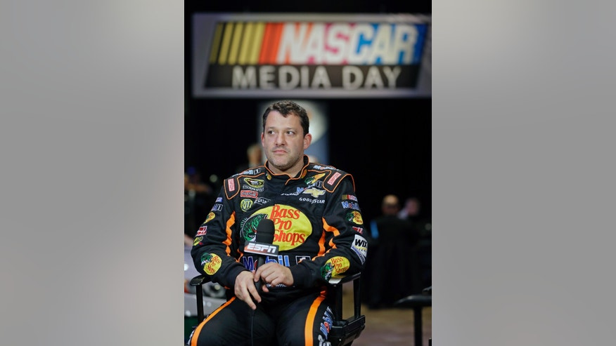 Tony Stewart waits his turn for a television interview during NASCAR media day at Daytona International Speedway, Thursday, Feb. 14, 2013, in Daytona Beach, Fla. (AP Photo/John Raoux)