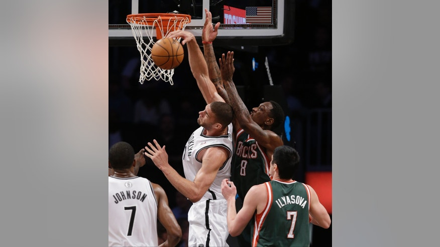 Brooklyn Nets center Brook Lopez (11) steals the ball from Milwaukee Bucks center Larry Sanders (8) as Nets guard Joe Johnson (7) and Bucks forward Ersan Ilyasova (7) watch in the first half of their NBA basketball game at Barclays Center, Tuesday, Feb. 19, 2013, in New York. (AP Photo/Kathy Willens)