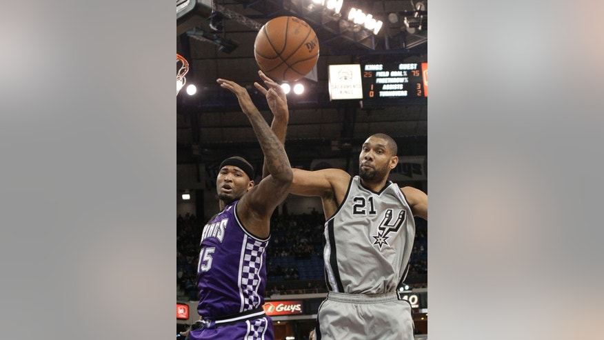 Sacramento Kings center DeMarcus Cousins, left, and San Antonio Spurs forward Tim Duncan go after a rebound during the first quarter of an NBA basketball game in Sacramento, Calif., Tuesday, Feb. 19, 2013. (AP Photo/Rich Pedroncelli)