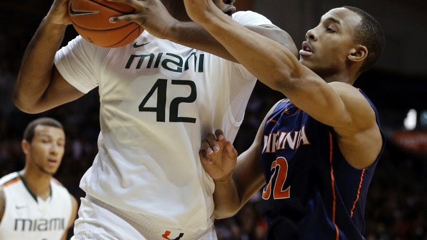 Virginia's Darion Atkins (32) blocks Miami's Reggie Johnson (42) during the first half of an NCAA college basketball game in Coral Gables, Fla., Tuesday, Feb. 19, 2013. (AP Photo/J Pat Carter)