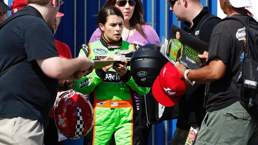 Daytona 500 pole sitter Danica Patrick signs autographs for fans before the NASCAR Sprint Cup Series Budweiser Duel 1 auto race Thursday, Feb. 21, 2013, at the Daytona International Speedway in Daytona Beach, Fla. (AP Photo/Terry Renna)