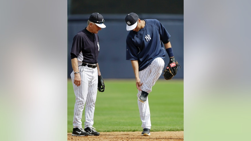 New York Yankees' Derek Jeter, right, points to his ankle as he talks with first base coach Mick Kelleher during a workout at baseball spring training, Wednesday, Feb. 20, 2013, in Tampa, Fla. (AP Photo/Matt Slocum)