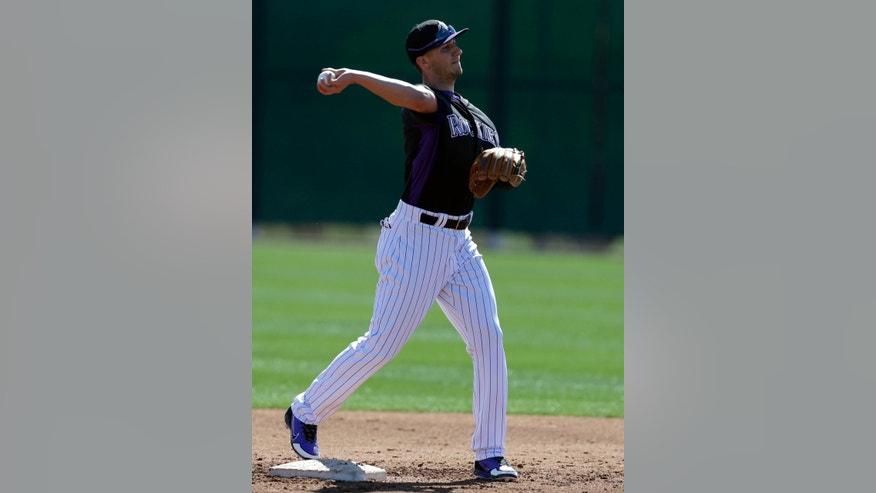 Colorado Rockies' Troy Tulowitzki throws to first base during a spring training baseball workout on Sunday, Feb. 17, 2013, in Scottsdale, Ariz. (AP Photo/Darron Cummings)