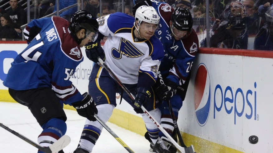 St. Louis Blues defenseman Ian Cole (28) flips the puck away from Colorado Avalanche right wing David Jones (54) and center Paul Stastny (26) during the first period of an NHL hockey game, Wednesday, Feb. 20, 2013, in Denver. (AP Photo/Joe Mahoney)