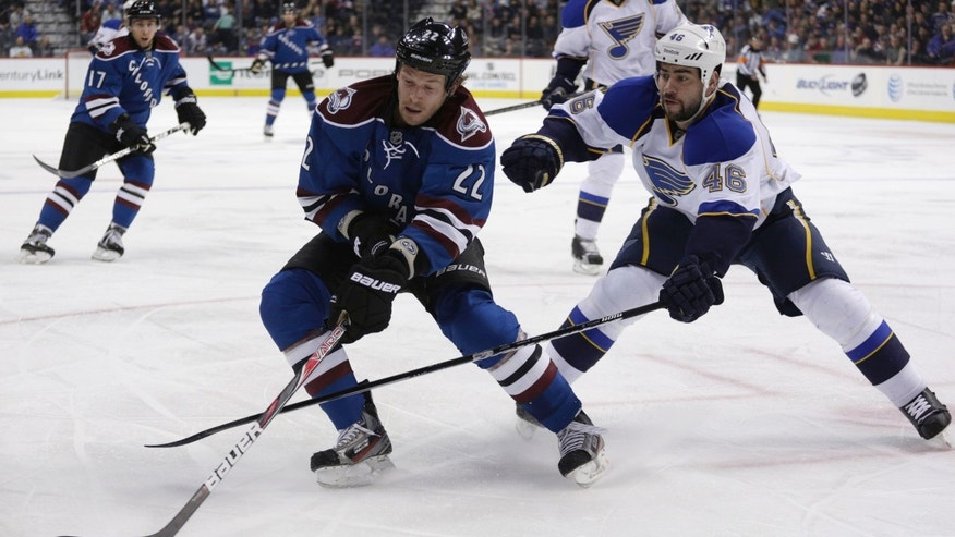 Colorado Avalanche defenseman Matt Hunwick (22) reaches for the puck against St. Louis Blues defenseman Roman Polak, of the Czech Republic, during the first period of an NHL hockey game, Wednesday, Feb. 20, 2013, in Denver. (AP Photo/Joe Mahoney)