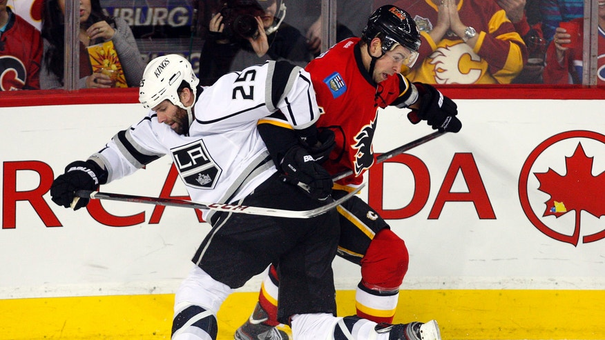 Los Angeles Kings' Dustin Penner, left, tangles with Calgary Flames' Chris Butler during third period NHL hockey action in Calgary, Alberta, Wednesday, Feb. 20, 2013. The Los Angeles Kings beat the Calgary Flames 3-1. (AP Photo/THE CANADIAN PRESS/Jeff McIntosh)
