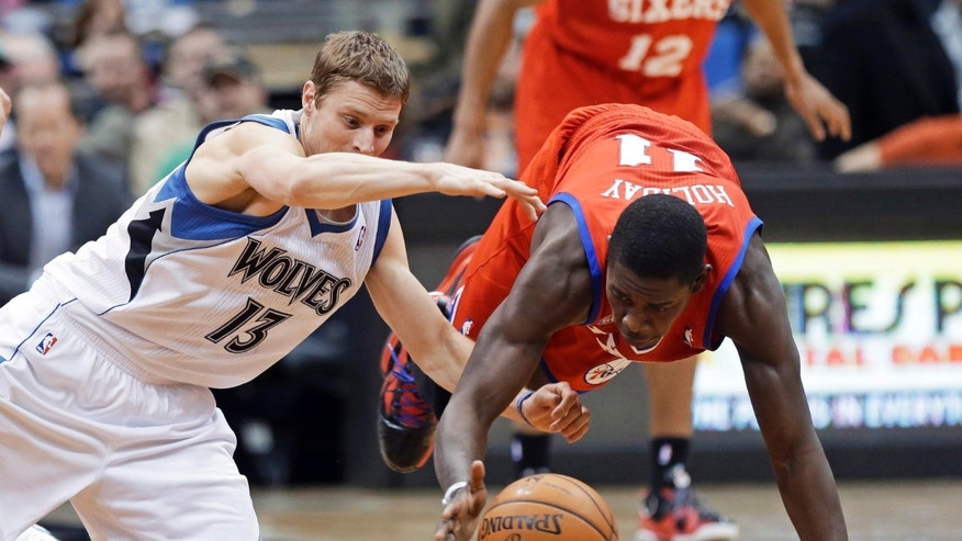 Minnesota Timberwolves' Luke Ridnour, left, and Philadelphia 76ers' Jrue Holiday scramble for the loose ball in the second half of an NBA basketball game Wednesday, Feb. 20, 2013, in Minneapolis. The Timberwolves  won 94-87. Holiday scored 16 points. (AP Photo/Jim Mone)