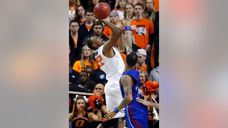 Oklahoma State guard Markel Brown (22) shoots in front of Kansas guard Travis Releford in the second half of an NCAA college basketball game in Stillwater, Okla., Wednesday, Feb. 20, 2013. Kansas won 68-67 in double overtime. (AP Photo/Sue Ogrocki)