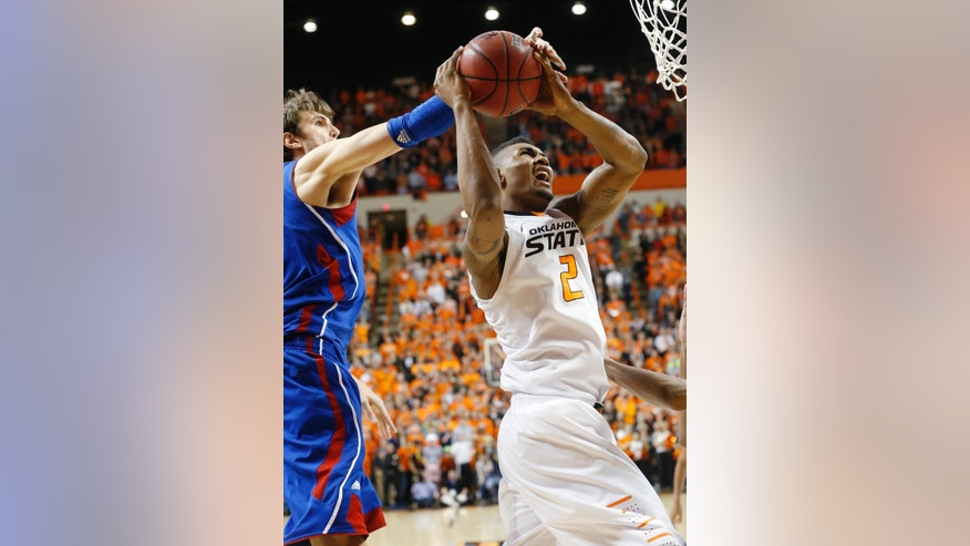 Kansas center Jeff Withey (5) reaches from behind to block a shot by Oklahoma State guard Le'Bryan Nash (2) in the second overtime of an NCAA college basketball game in Stillwater, Okla., Wednesday, Feb. 20, 2013. Kansas won in double overtime 68-67. (AP Photo/Sue Ogrocki)