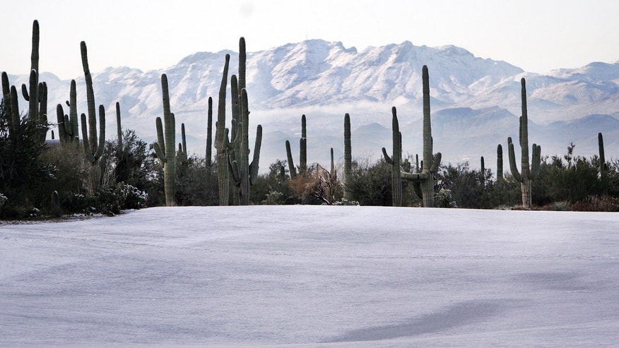 Snow covers a fairway in the morning hours before before play resumes for the first round of the Match Play Championship golf tournament, Thursday, Feb. 21, 2013, in Marana, Ariz.  A snow storm blanketed the course on Wednesday suspending the first round of play and postponing it until later in the day on Thursday. (AP Photo/Arizona Daily Star,  Mike Christy)  ALL LOCAL TV OUT; PAC-12 OUT; MANDATORY CREDIT, MAGS OUT, NO SALES