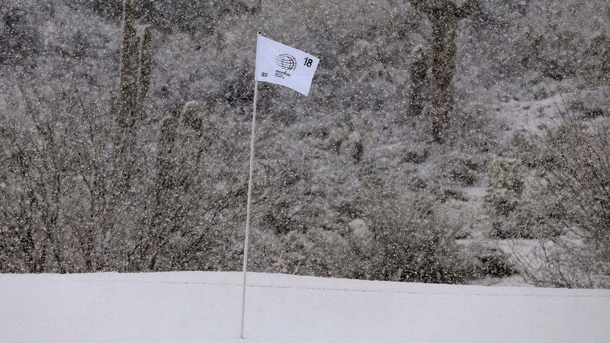 The pin flag on the 18th green blows in the falling snow during the Match Play Championship golf tournament, Wednesday, Feb. 20, 2013, in Marana, Ariz. Play was suspended for the rest of the day. (AP Photo/Julie Jacobson)