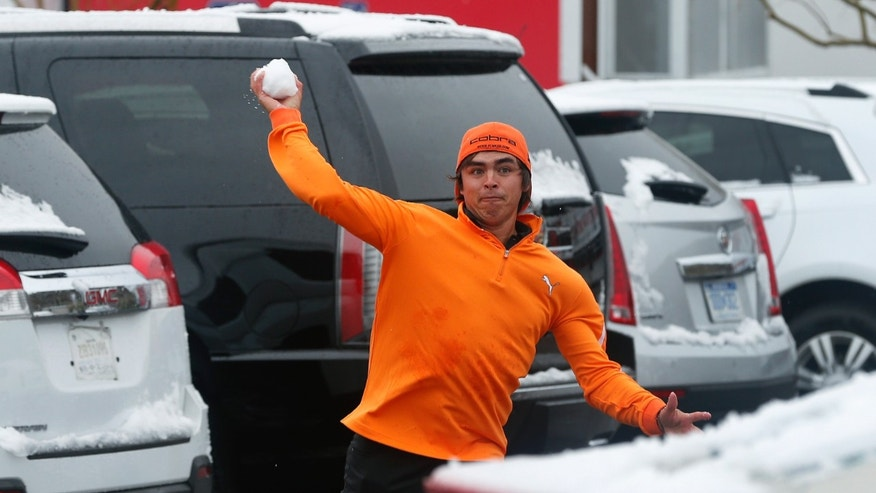 Rickie Fowler throws snowballs at fellow players in the parking lot after a snow storm suspended the Match Play Championship golf tournament, Wednesday, Feb. 20, 2013, in Marana, Ariz. Play was suspended for the day. (AP Photo/Ross D. Franklin)