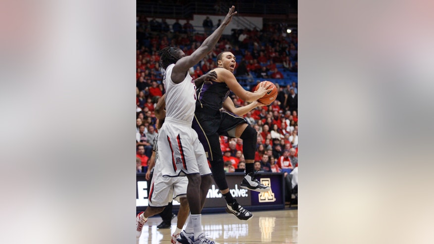 Washington's Perris Blackwell, right, looks to pass the ball around Arizona's Angelo Chol during the first half of an NCAA college basketball game at McKale Center in Tucson, Ariz., Wednesday, Feb. 20, 2013. (AP Photo/Wily Low)