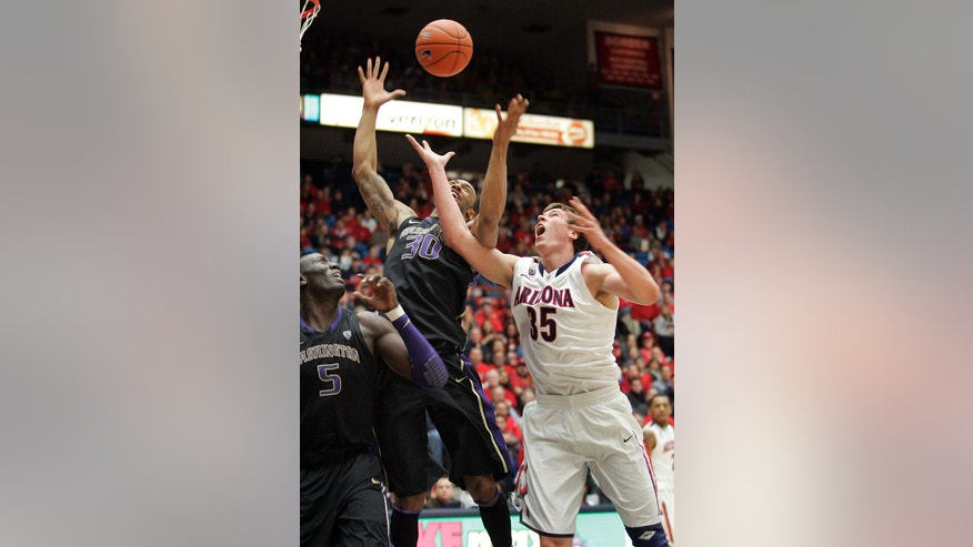 Arizona's Kaleb Tarczewski (35) and Washington's Desmond Simmons (30) look for a rebound during the first half of an NCAA college basketball game at McKale Center in Tucson, Ariz., Wednesday, Feb. 20, 2013. (AP Photo/John Miller)