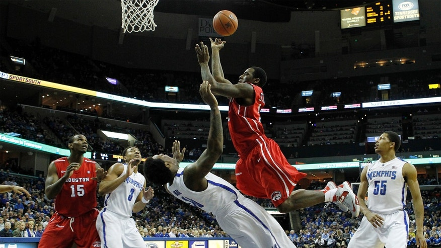 Houston guard Jherrod Stiggers (21) goes to the basket over Memphis defenders Tarik Black (10), Chris Crawford (3) and Geron Johnson (55) during the first half of an NCAA college basketball game on Wednesday, Feb. 20, 2013, in Memphis, Tenn. (AP Photo/Lance Murphey)