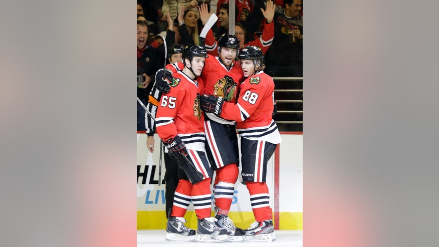 Chicago Blackhawks' Viktor Stalberg, center, celebrates with Andrew Shaw, left, and Patrick Kane after scoring a goal during the second period of an NHL hockey game against the San Jose Sharks in Chicago, Friday, Feb. 22, 2013. (AP Photo/Nam Y. Huh)