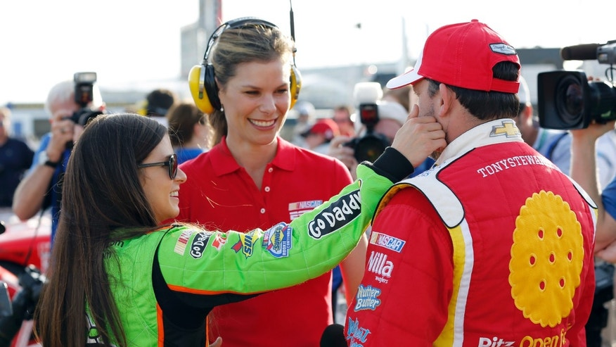 Danica Patrick, left, reaches out to feel Tony Stewart's beard after their qualifying runs for the NASCAR Nationwide Series auto race Friday, Feb. 22, 2013, at Daytona International Speedway in Daytona Beach, Fla. (AP Photo/Terry Renna)