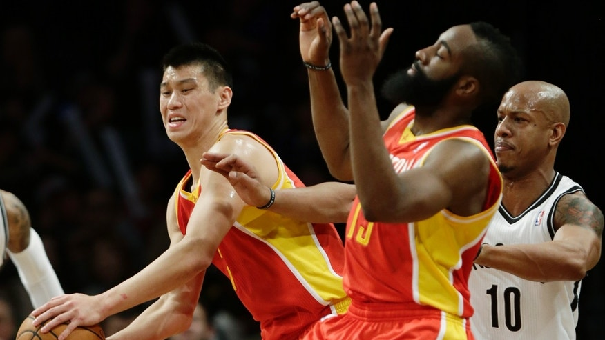 Houston Rockets' Jeremy Lin, left, and teammate James Harden, center, collide as Brooklyn Nets' Keith Bogans, right, defends him during the first half of an NBA basketball game, Friday, Feb. 22, 2013, in New York.  (AP Photo/Frank Franklin II)