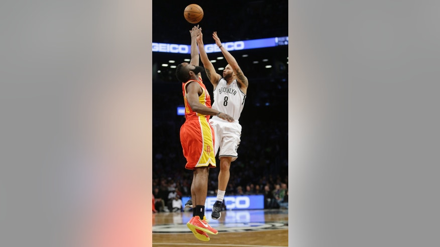 Brooklyn Nets' Deron Williams (8) shoots over Houston Rockets' James Harden (13) during the first half of an NBA basketball game, Friday, Feb. 22, 2013, in New York. (AP Photo/Frank Franklin II)