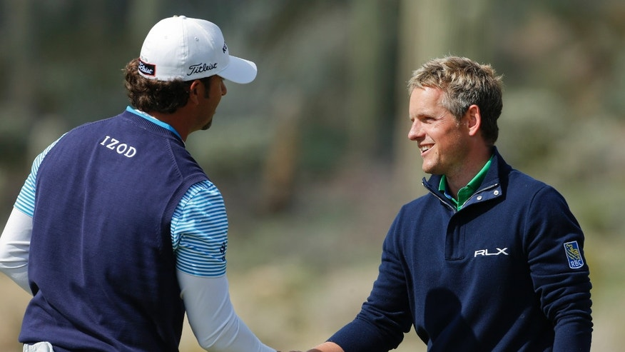 England's Luke Donald, right, congratulates Scott Piercy after losing 7 and 6 to Piercy in the second round of the Match Play Championship golf tournament, Friday, Feb. 22, 2013, in Marana, Ariz. (AP Photo/Ross D. Franklin)