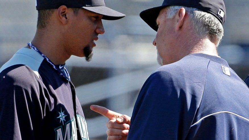 Seattle Mariners pitching coach Carl Willis talks to starting pitcher Hector Noesi during the first inning of an exhibition spring training baseball game against the San Diego Padres Friday, Feb. 22, 2013, in Peoria, Ariz. (AP Photo/Charlie Riedel)