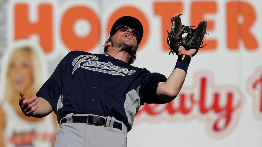 San Diego Padres left fielder Travis Buck catches a fly ball hit by Seattle Mariners' Kyle Seager for an out during an exhibition baseball game Friday, Feb. 22, 2013, in Peoria, Ariz. (AP Photo/Charlie Riedel)