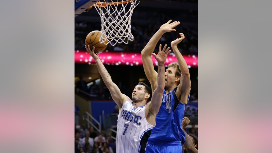 FILE - In this Jan. 20, 2013 file photo, Orlando Magic's J.J. Redick (7) shoots in front of Dallas Mavericks' Dirk Nowitzki, of Germany, during the second half of an NBA basketball game in Orlando, Fla. A person familiar with the situation says the Orlando Magic have agreed to trade veteran shooting guard Redick, center Gustavo Ayon and reserve point guard Ish Smith to the Milwaukee Bucks in exchange for guards Doron Lamb and Beno Udrih, as well as forward Tobias Harris. The person spoke to The Associated Press Thursday, Feb. 21, 2013 on condition of anonymity because the deal was not officially complete. (AP Photo/John Raoux, File)