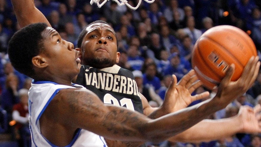 Kentucky's Archie Goodwin, left, shoots under pressure from Vanderbilt's Sheldon Jeter during the second half of an NCAA college basketball game at Rupp Arena in Lexington, Ky., Wednesday, Feb. 20, 2013. Kentucky defeated Vanderbilt 74-70. (AP Photo/James Crisp)